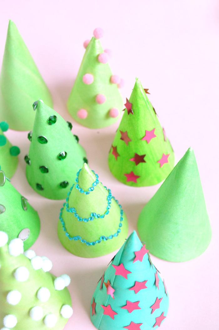 Kleine Kegel aus Karton ausschneiden und grün ausmalen, mit Sternen, Perlen und Bommeln dekorieren