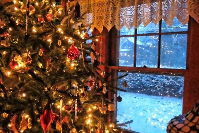 beleuchtete-weihnachtsdeko-am-fenster-großartiger-tannenbaum