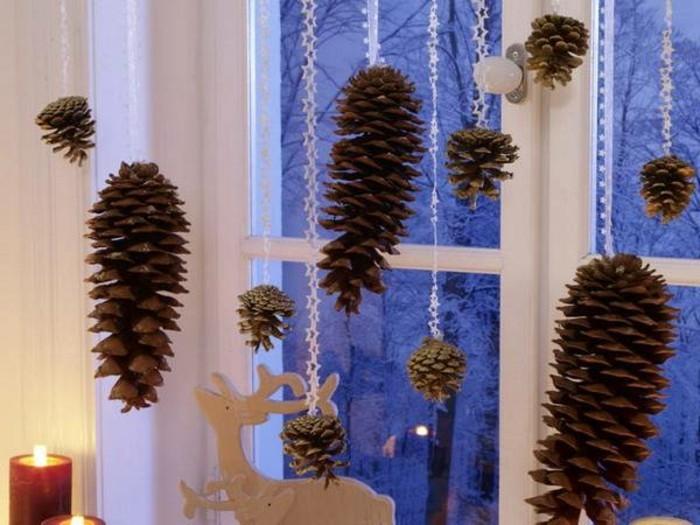 beleuchtete-weihnachtsdeko-am-fenster-hängende-zapfen
