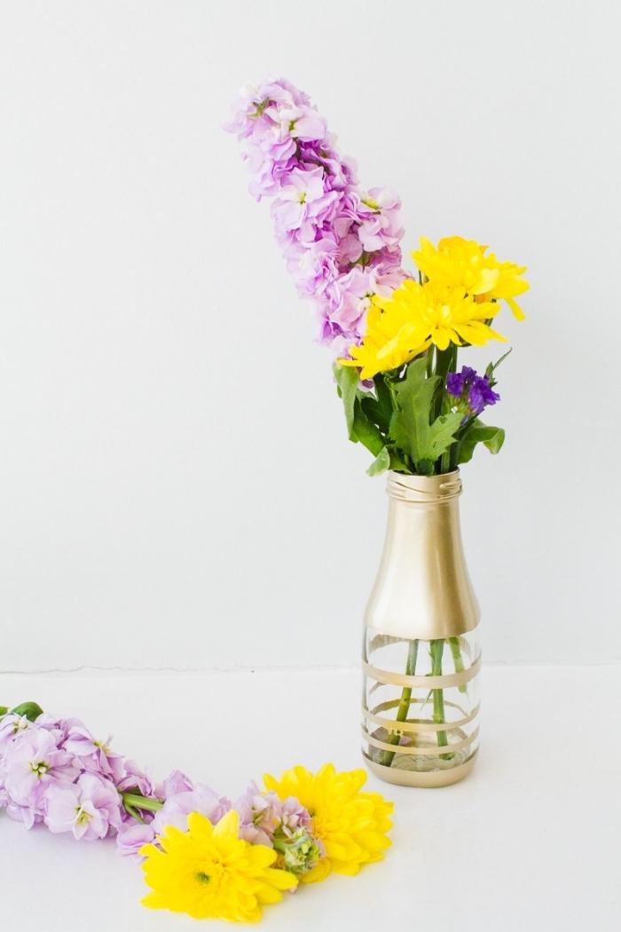 glasvase dkeoriert mit goldener farbe, deko tisch, rosa und lila blumen, frühlingsdeko