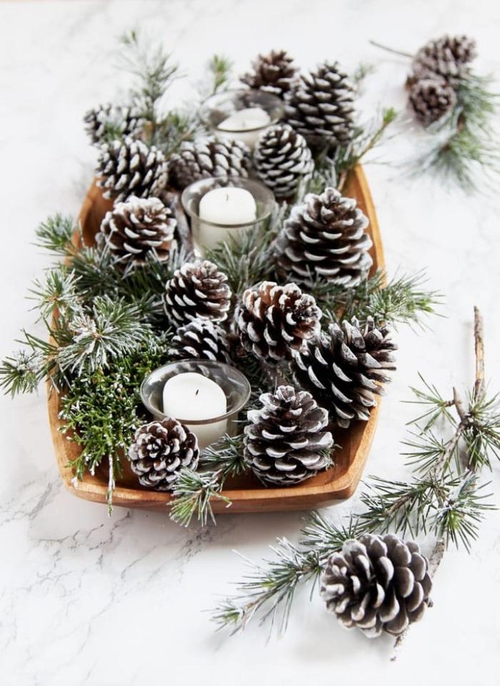 holzplatte mit kerzen und tannenzapfen, grüne zweige, esstisch deko ideen zu weihnachten, eifnach
