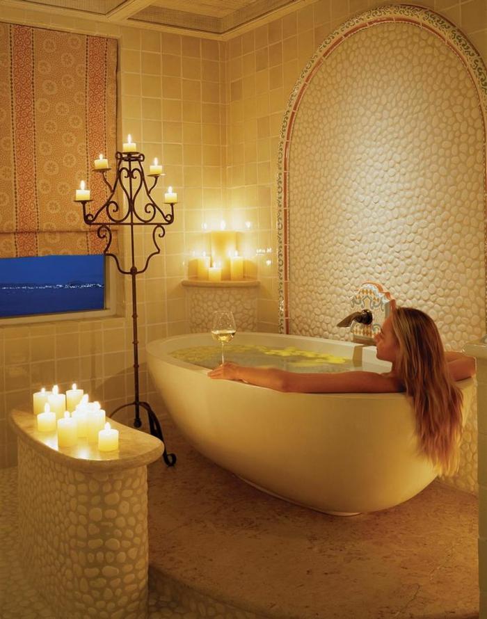 exotisches-extravagantes-Badezimmer-Interieur-Fliesen-dekorative-Steine-Wandgestaltung-freistehende-badewanne-oval-Kerzen