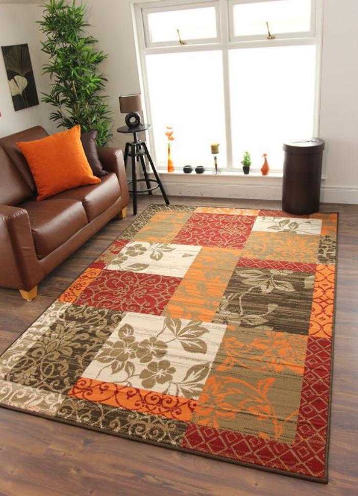 gemütliches-Wohnzimmer-Ledersofa-orange-Kissen-retro-teppich