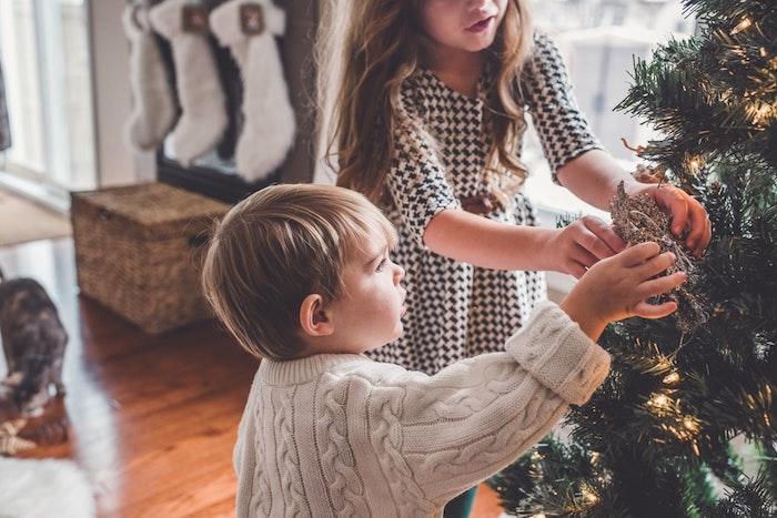 Kleiner Junge und seine Schwester schmücken den Weihnachtsbaum, Weihnachtsbasteln mit Kindern
