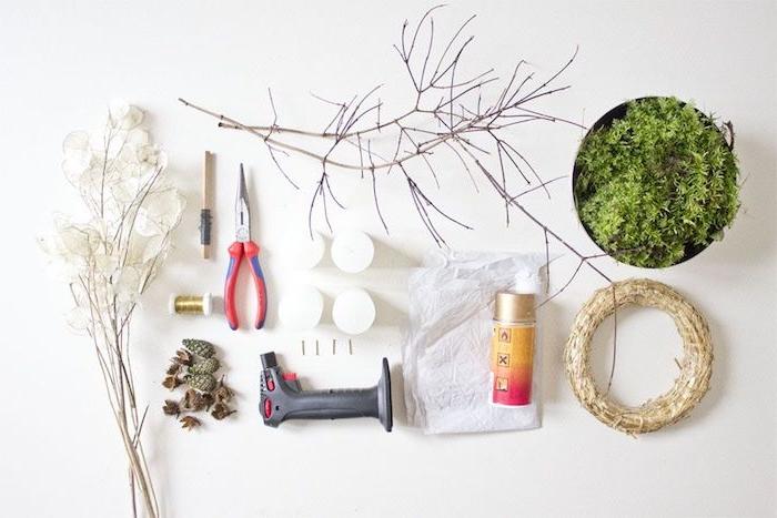 Materialien für DIY Adventskranz, Moos und Zweige, dünner Draht und Heißklebepistole, Tannenzapfen und Spray