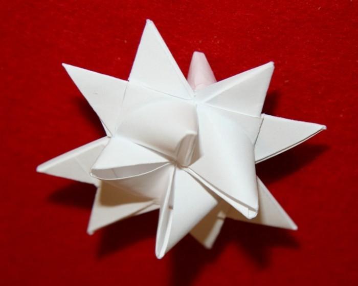 sterne-falten-aus-papier-weißes-tolles-modell-roter-hintergrund