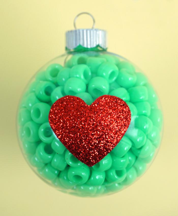 Durchsichtige Christbaumkugel aus Glas mit grünen Perlen füllen, rotes Glitzer Herz aufkleben