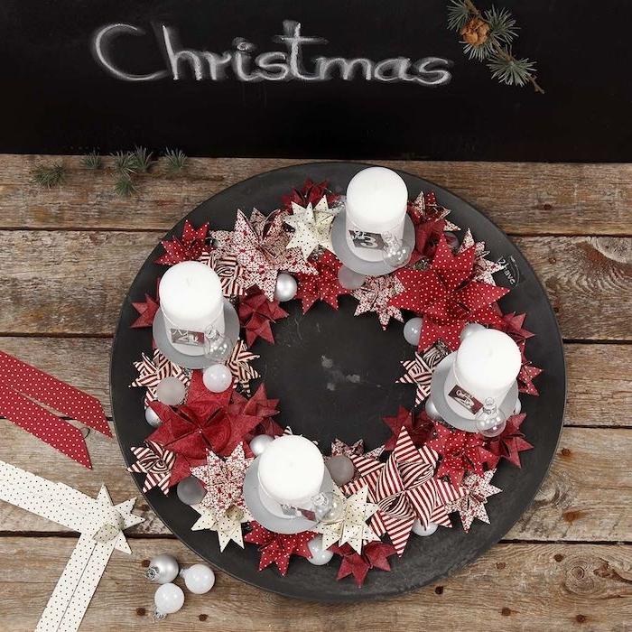DIY Adventskranz mit weißen und roten Papiersternen, weiße Kerzen mit Nummernschilder und durchsichtigen Christbaumkugeln