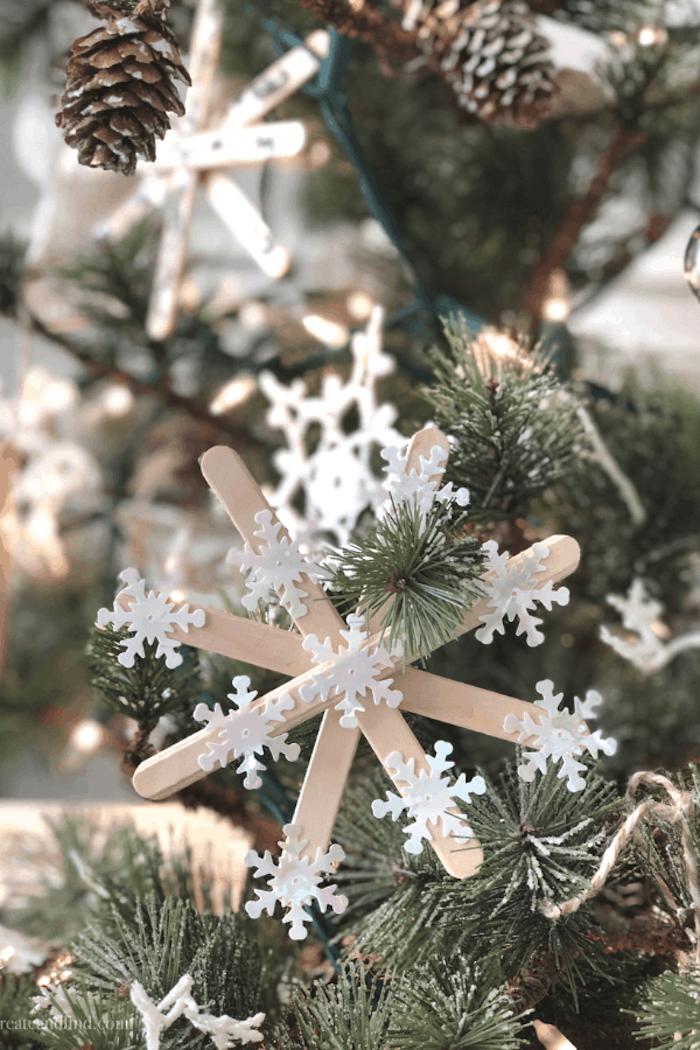 Schneeflocke selber machen aus Eisstielen, mit kleinen Schneeflocken aus Papier verzieren