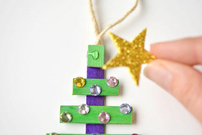 Weihnachtsbaum aus Eisstielen mit kleinen Perlen und Glitzerstern verzieren