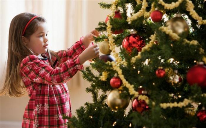 Weihnachtsbaum schmücken – goldene Glaskugeln auf hellem Untergrund