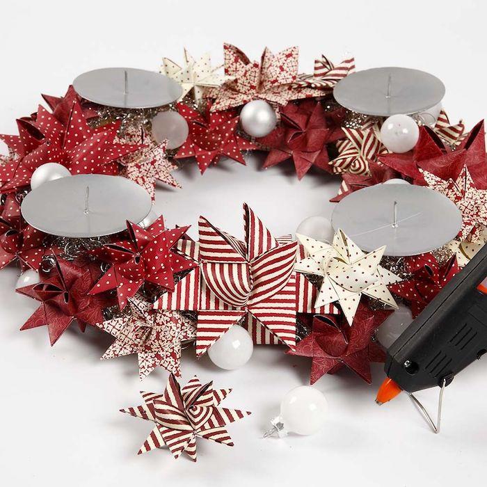 Adventskranz selber machen Schritt für Schritt, weiße und rote Papiersterne und kleine Christbaumkugeln aufkleben