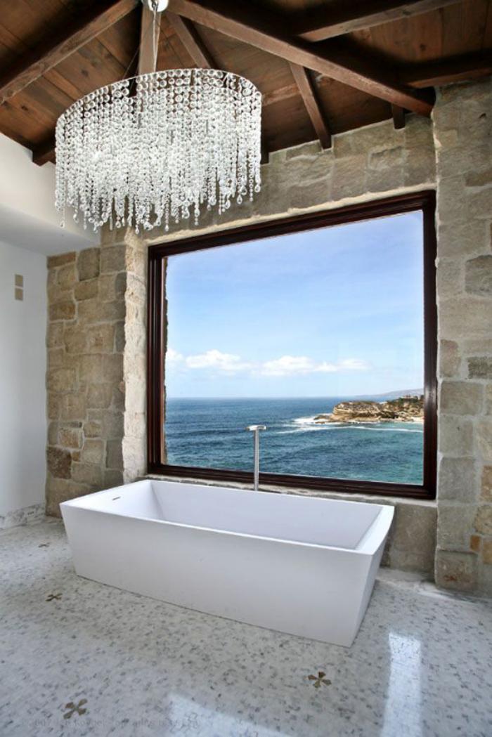 Badezimmer-mit-schönem-Ausblick-in-rustikalem-Stil-Steinwand-hölzerne-Zimmerdecke-wundervoller-Kristall-Kronleuchter