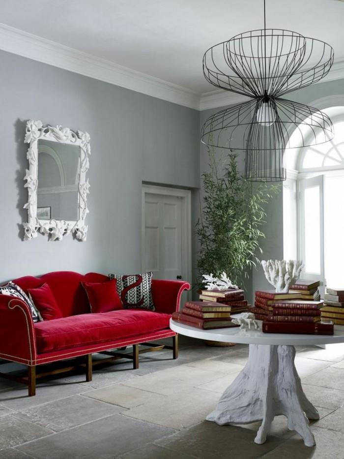 Designer-Wohnung-feine-Möbel-interessante-Leuchte-Spiegelrahmen-mit-Ornamenten-rotes-Sofa-aus-Samt