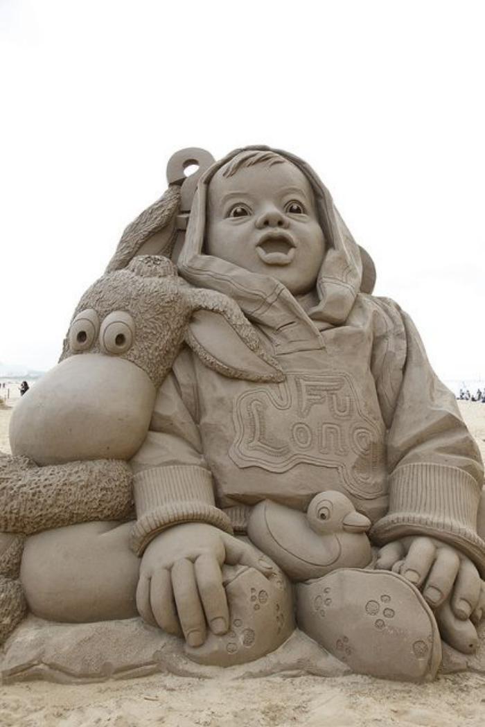 Kunst-Skulptur-aus-Sand-Kind-mit-seinen-Spielzeugen
