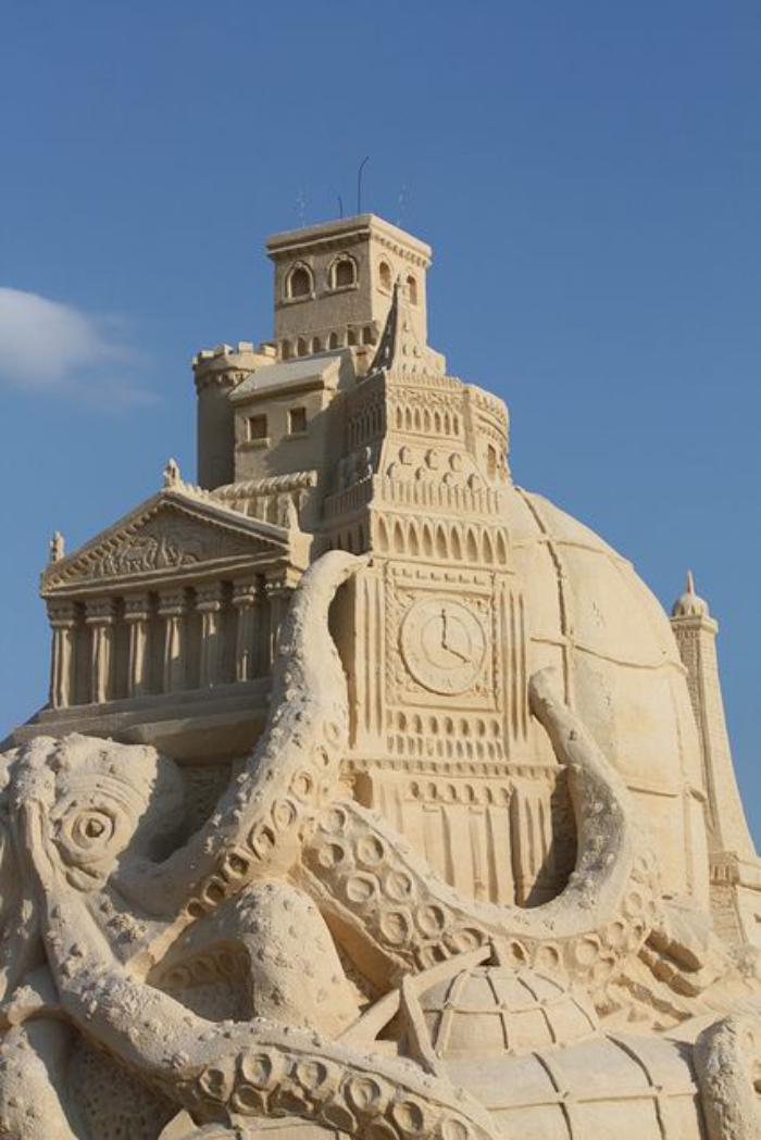 Sandskulptur-von-Oktopode-haltend-großes-Gebäude