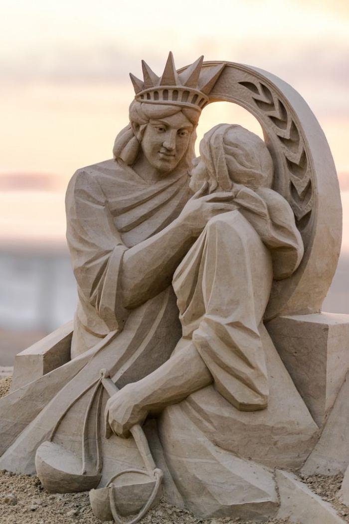 Sandskulptur-von-der-Statue-der-Freiheit-umarmend-die-Statue-der-Gerechtigkeit