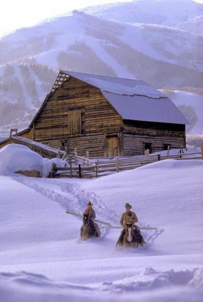 Winterbild-Dorf-im-Gebirge-Pferde-reiten-durch-den-Schnee