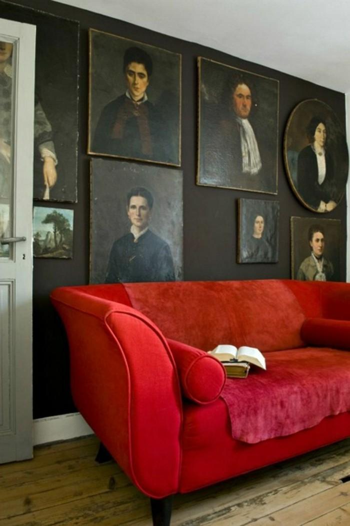 Zimmer-mit-vielen-Portraits-an-der-Wand-Sofa-rot