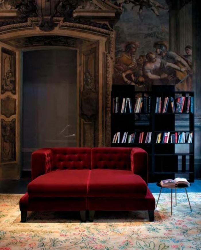 aristokatische-Wohnung-Bücherregale-Wandgestaltung-mit-historischen-Motiven-rote-Couch-aus-Samt