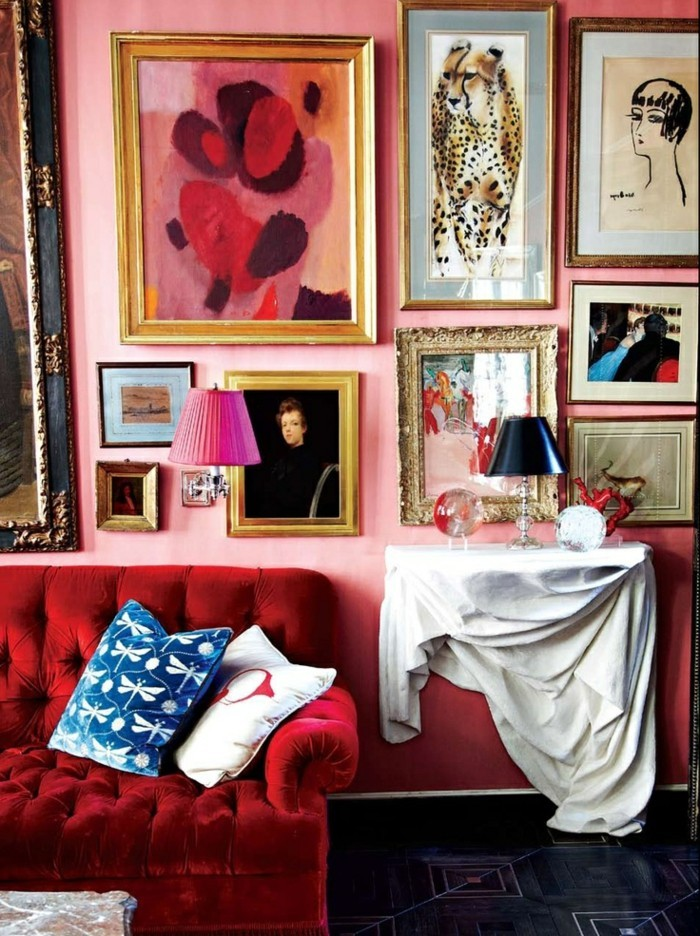 artistische-Wohnung-feine-Wandbilder-rosa-Wand-attraktives-rotes-Sofa