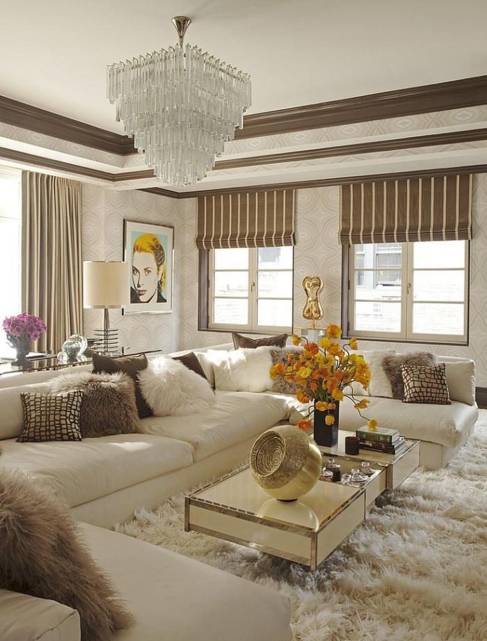 artistisches-Interieur-Portrait-an-der-Wand-flaumiger-Teppich-extravagante-Kissen-prachtvoller-Kristall-Kronleuchter