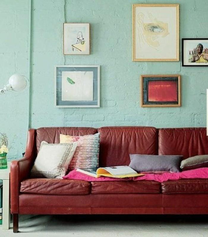 artistisches-Interieur-Wandbilder-Ziegelwand-in-Minze-Farbe-rotes-Ledersofa