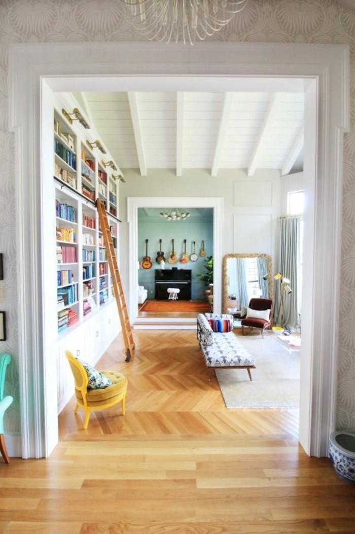 artistisches-Interieur-farbige-Akzente-große-Bücherwand-Parkett