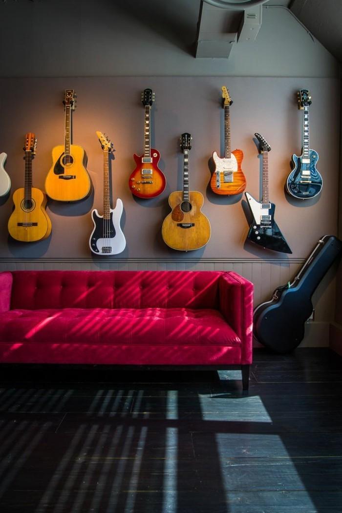 artistisches-Interieur-viele-Gitarren-hängend-an-der-Wand-schlichtes-Modell-rote-Couch