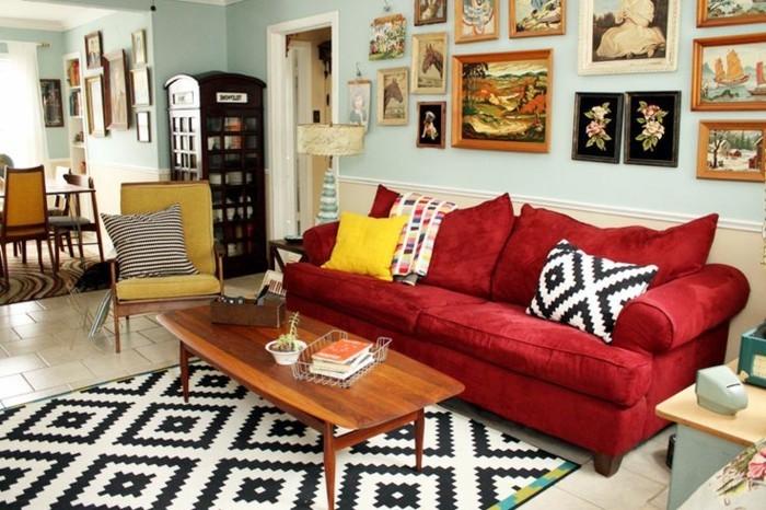 artistisches-Wohnzimmer-schöne-Wandbilder-graphischer-Teppich-Kissen-rotes-Sofa