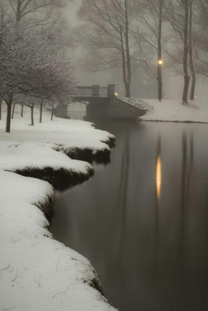 beeindruckendes-Winterbild-See-Schnee-Wasser-Brücke-dunkles-nostalgisches-Foto