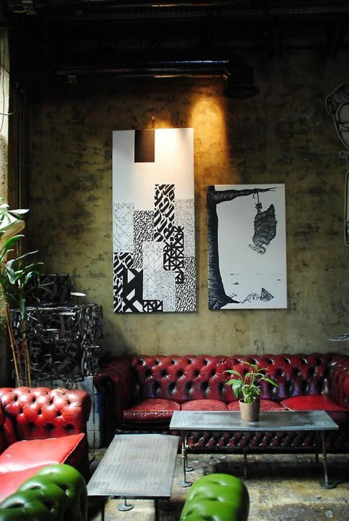 dunkles-männliches-Interieur-Wände-aus-Beton-Topfpflanzen-Chesterfield-Ledersofa-rot