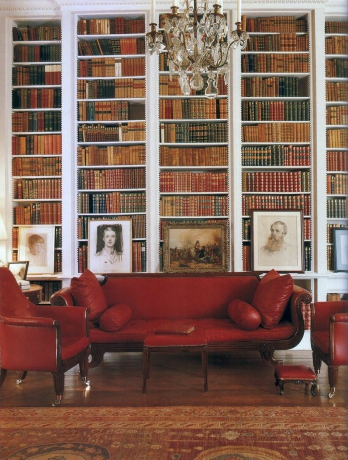 elegantes-Interieur-Bücherwand-Portraits-rote-Ledercouch-Sessel