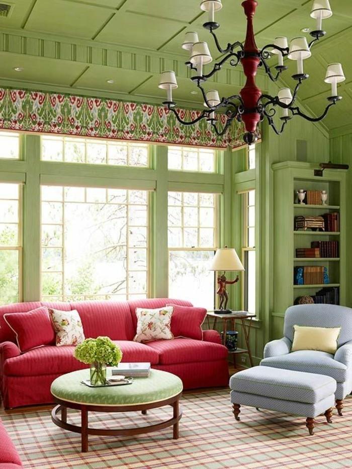 gemütliches-Wohnzimmer-Interieur-grüne-Wände-Zimmerdecke-blauer-Sessel-rote-Couch-farbige-Akzente