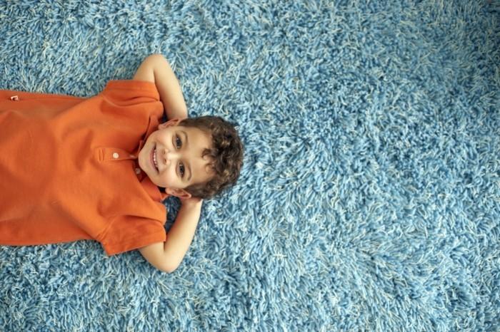 unikales foto von einem kleinen jungen auf dem boden - blauer teppich
