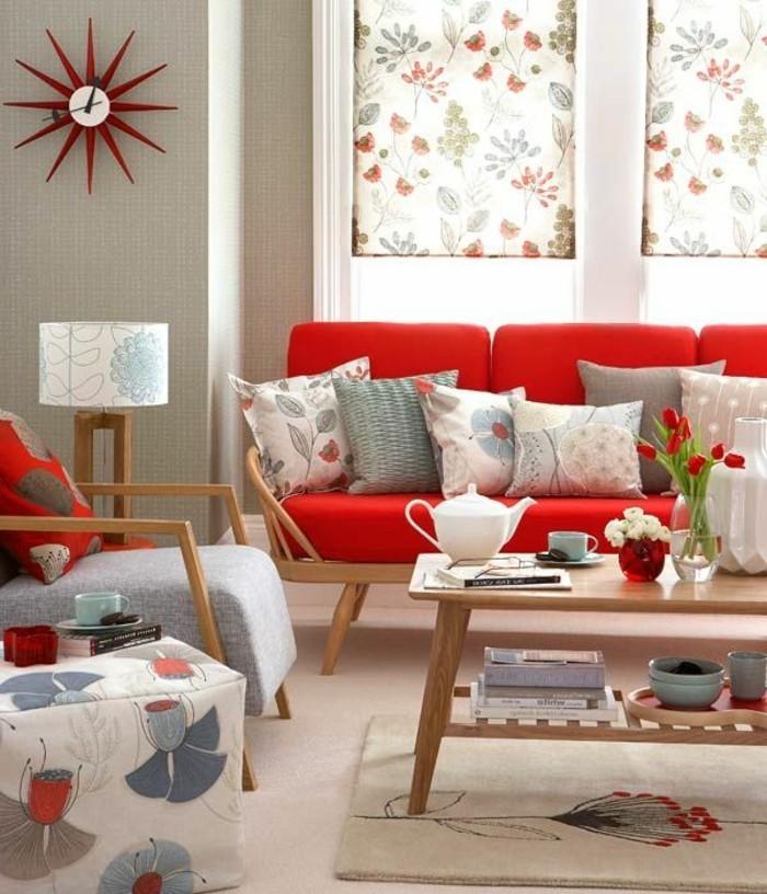 moderne-Ausstattung-Muster-mit-floralen-Motiven-hölzerner-Kaffeetisch-rote-Tulpen-interessante-Wanduhr-rote-Couch
