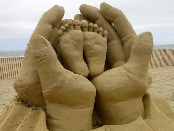 moderne-Skulptur-aus-Sand-Kinder-Füße-in-den-Händen-vom-Vater