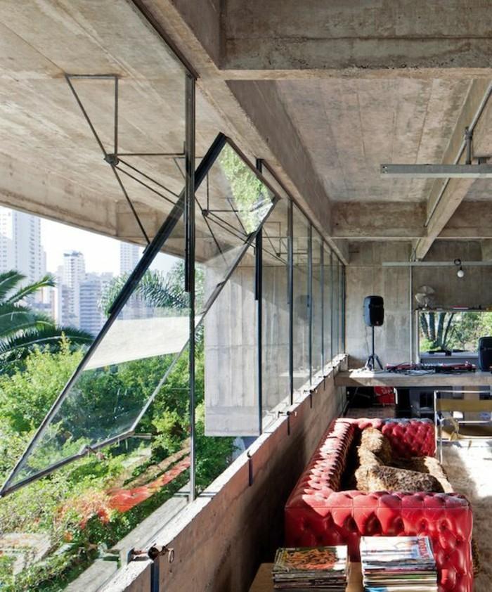 moderne-Wohnung-aus-Beton-und-Glas-rotes-Ledersofa-mit-Knöpfen