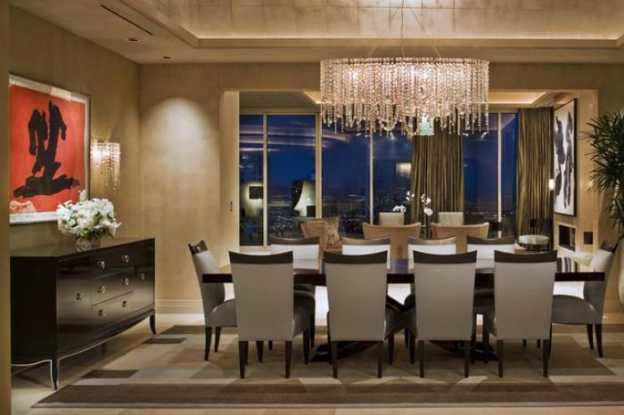 modernes-Esszimmer-Interieur-interessantes-Wandbild-schwarze-Kommode-großer-Kristall-Kronleuchter