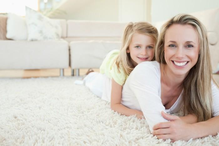 mutti-und-kind-liegen-auf-dem-weißen-teppich-im-wohnzimmer