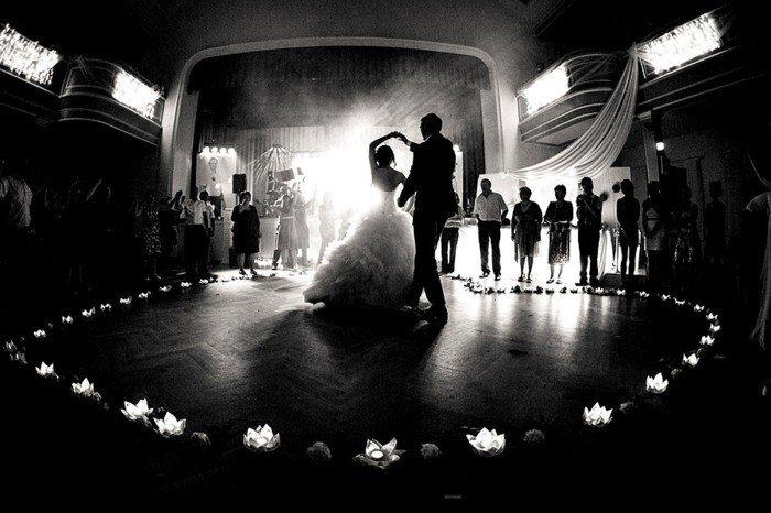 romantisches-Hochzeitsbild-der-erste-Tanz-Brautleute-umgeben-von-den-Gästen-Blumen-Kerzen