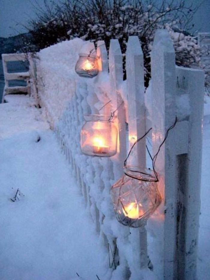 romantisches-Winterbild-Zaun-mit-Laternen-im-Schnee