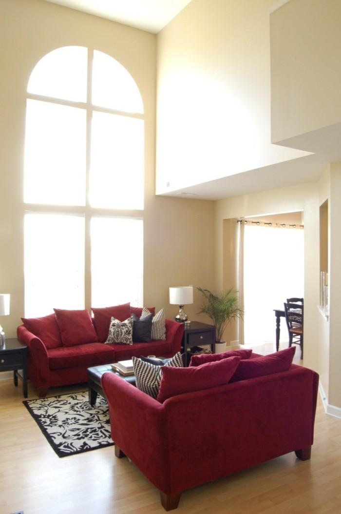 schlichtes-Interieur-kleine-rote-Sofas-schwarz-weiße-Kissen