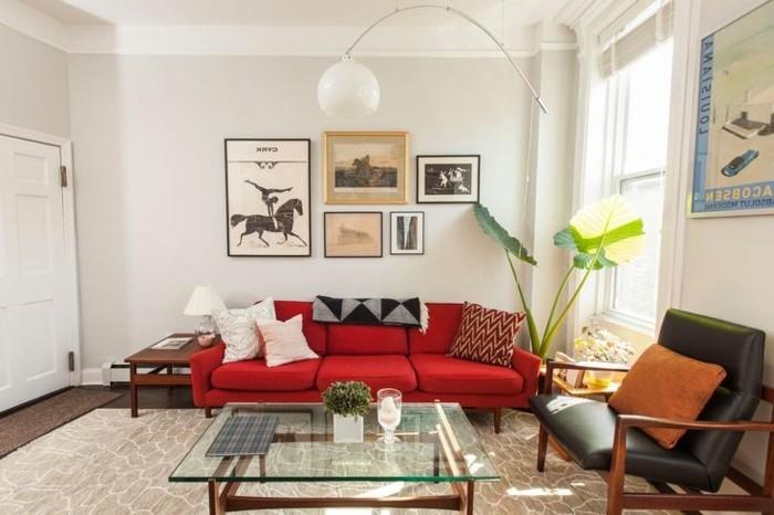 schlichtes-Interieur-weiße-Wände-Topfpflanze-Designer-Leuchte-schwarzer-Ledersessel-rote-Couch-gläserner-Kaffeetisch
