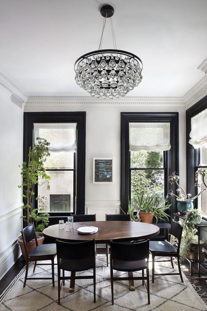 schwarz-weißes-Esszimmer-Interieur-ovaler-Esstisch-simpler-eleganter-Kristallleuchter
