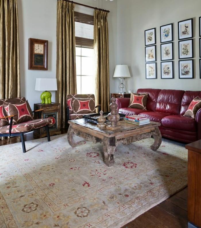 vintage-Interieur-Kaffeetisch-aus-Massivholz-Teppich-mit-ethnischen-Motiven-kleine-Wandbilder-rote-Ledercouch