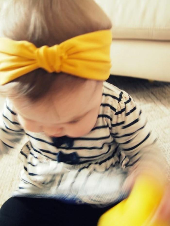 Baby-mit-kokettem-gelben-Haaraccessoire