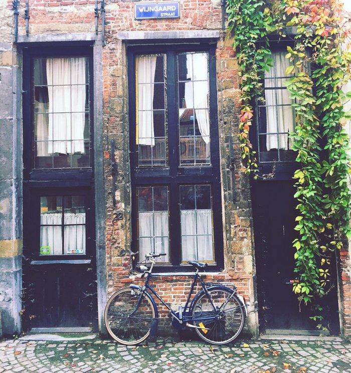 Fahrrad-neben-hohem-alten-Haus