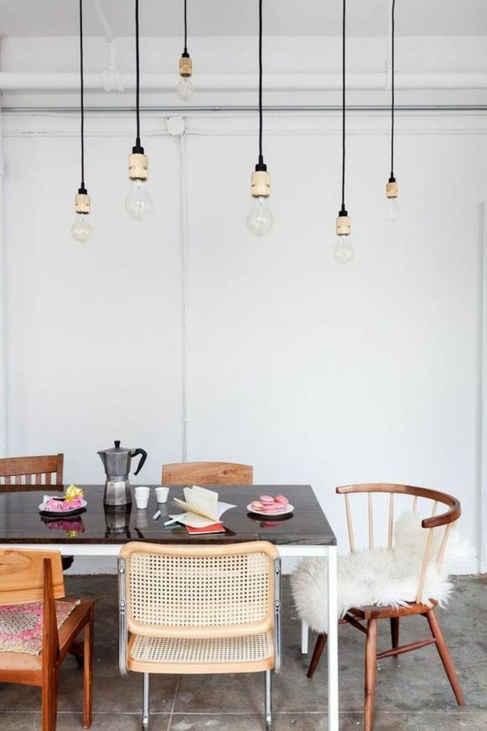 anspruchsloses-Interieur-hängende-Glühbirnen-verschiedenartige-vintage-Stühle