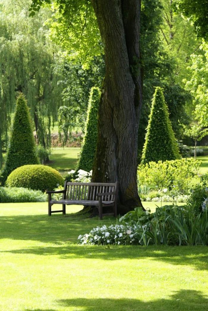 fantastischer-grüner-Garten-einsame-Gartenbank-unter-dem-Baum